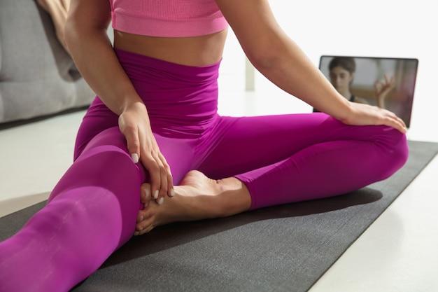 Ноги. закройте вверх красивой молодой женщины, работающей в помещении, делая упражнения йоги на сером циновке, деталях. практика неузнаваемой кавказской модели. концепция здорового образа жизни, внимательности, баланса.