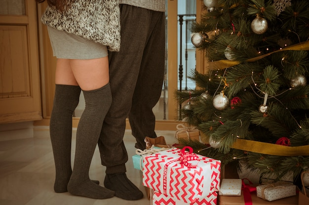 Legs of couple standing near christmas tree