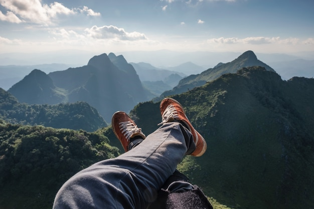 Legs cross traveler relaxing and hanging on cliff with evergreen mountain