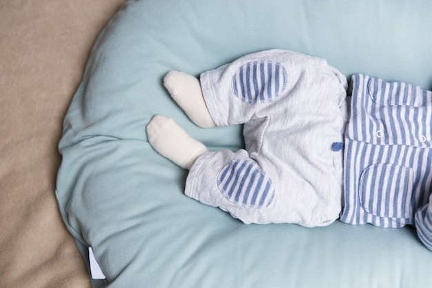 Legs and feet of baby lying on soft blue mattress