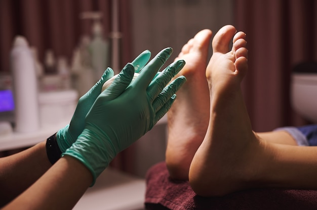 Legs of female client getting pedicure treatment from professional master in beauty salon. pedicure concept