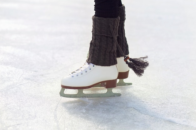 Legs in figure skates are on the ice on the rink. classic white figure skates close-up. knitted warm leg warmers with tassels