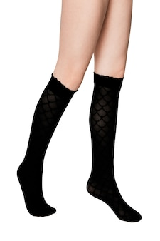 Legs of a girl in black socks on a white background