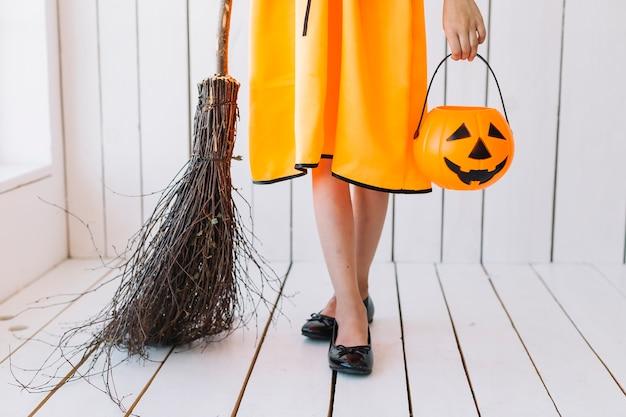 Gambe della ragazza con cesto e scopa di halloween