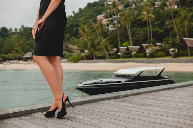 Gambe in scarpe nere col tacco alto della donna attraente sexy di lusso vestita in abito nero in posa sul molo in hotel resort di lusso, vacanze estive, spiaggia tropicale