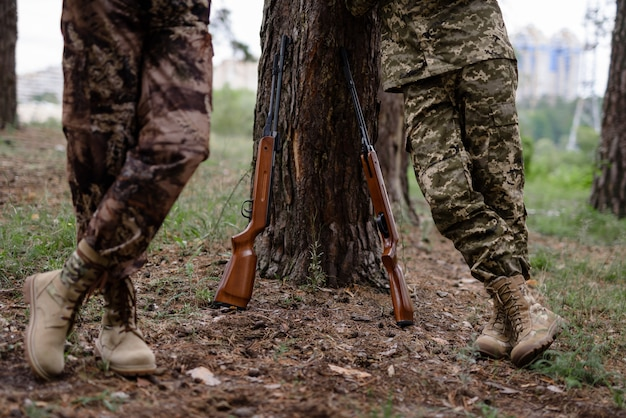 Legs of hunters standing leaning to tree rifles