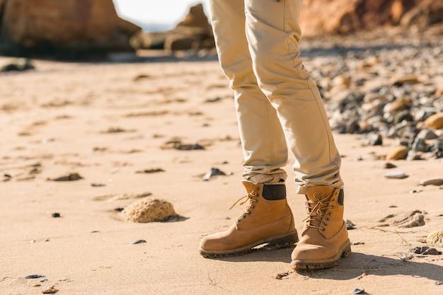 暖かいジャケットと帽子を身に着けている秋の海岸でバックパックを持って旅行する若いヒップスターの男のブーツの靴の脚