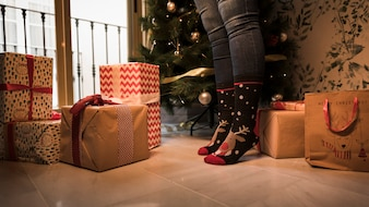 Legs in Christmas socks between present boxes and decorated fir tree
