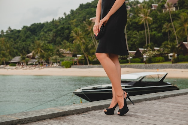 高級リゾートホテル、夏休み、熱帯のビーチの桟橋でポーズをとって黒いドレスに身を包んだ豪華なセクシーな魅力的な女性のハイヒールの黒い靴の足