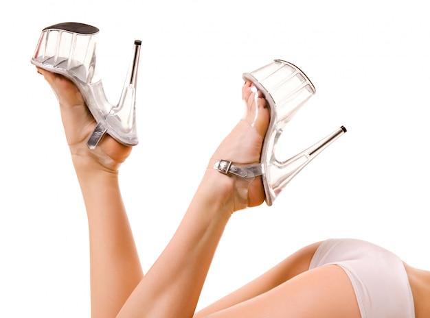 ハイヒールの靴と白い背景で隔離された若い女性ダンサーのショートパンツで戦利品の足