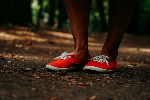 공원의 가을 길에 빨간 운동화를 신고 있는 다리. 검은색 가죽 다리. 여름 숲에서 스포츠