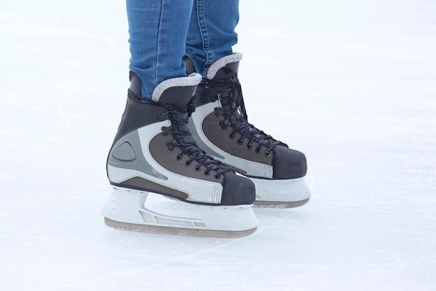 스케이트의 다리는 아이스 링크 클로즈업에서 활발하게 스케이트를 타고 있습니다. 취미와 스포츠. 휴가 및 겨울 활동.
