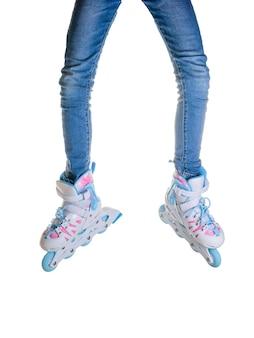 白い表面に分離されたスキニージーンズとローラースケートの脚