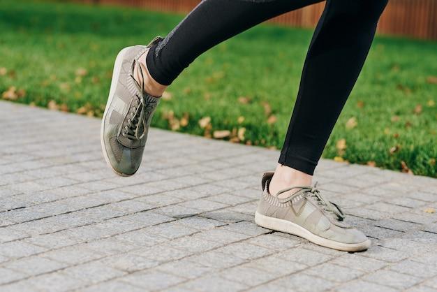 自然の中の公園で長距離を走るスニーカーと黒のレギンスの足。