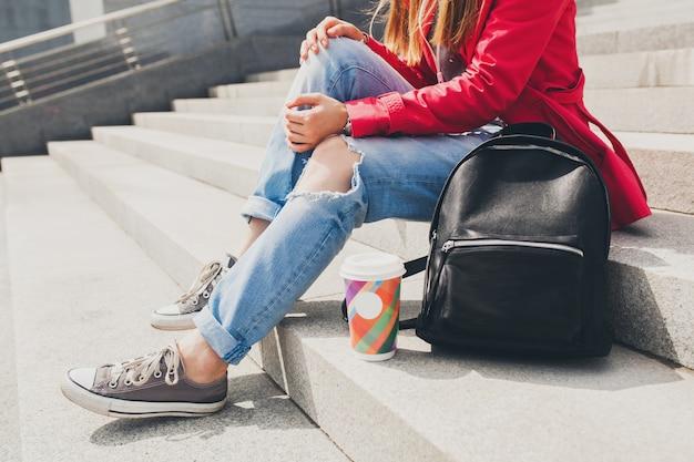 バックパックとコーヒーの大都市都会的なスタイルのトレンドが付いている通りにピンクのコートを着た若い流行に敏感な女性のスニーカーシューズトレンドの足