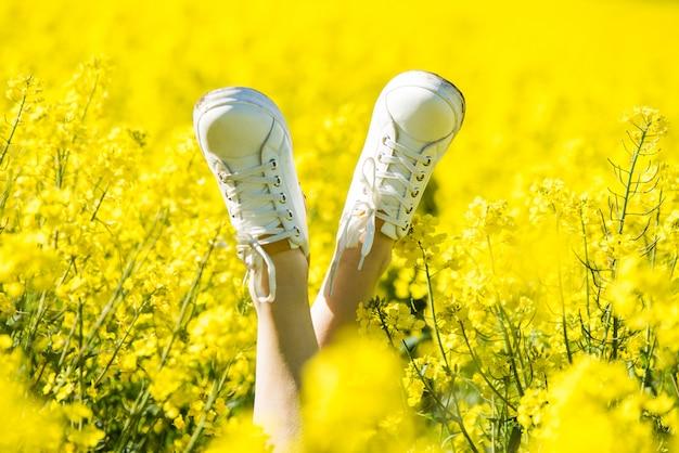 黄色のフィールドでスニーカーの足。レッグアップ。