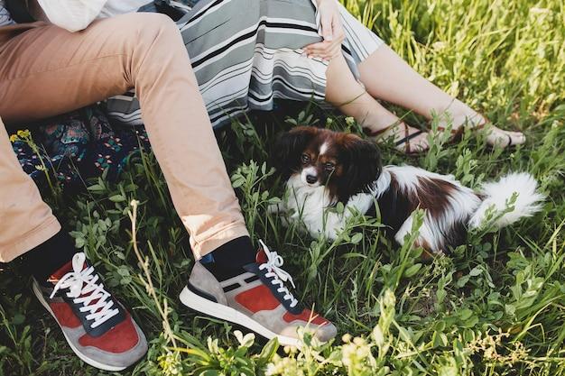 草に座っているスニーカーの足田舎で犬を連れて歩いて恋にスタイリッシュな流行に敏感な若いカップル、夏の自由奔放に生きるファッション、ロマンチックな