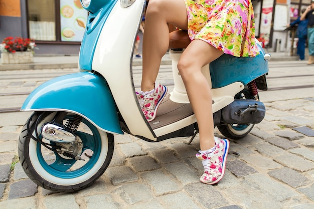 バイクの街の通りに乗っている若い美しい女性のスニーカーの足