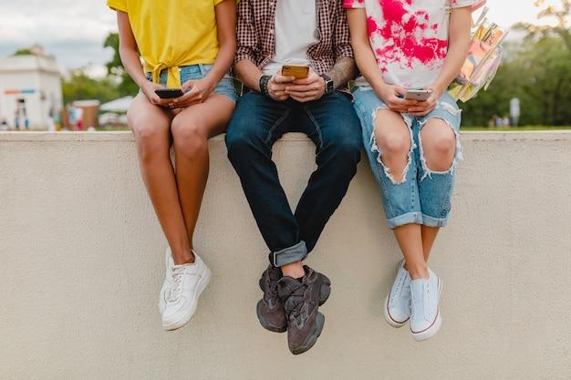 スマートフォンを使って公園に座っている友人の若い会社のスニーカーの脚