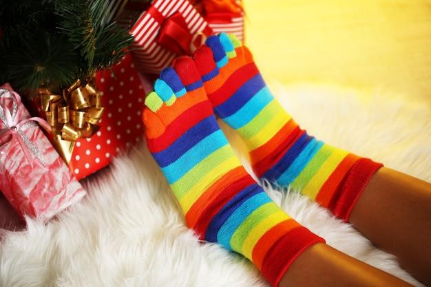 カーピングされたクリスマスツリーの近くの靴下の足