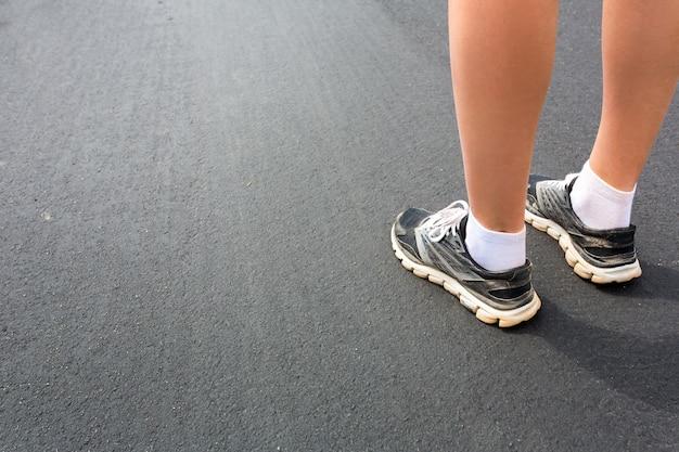 Ноги в спортивной обуви на асфальтовой дороге крупным планом