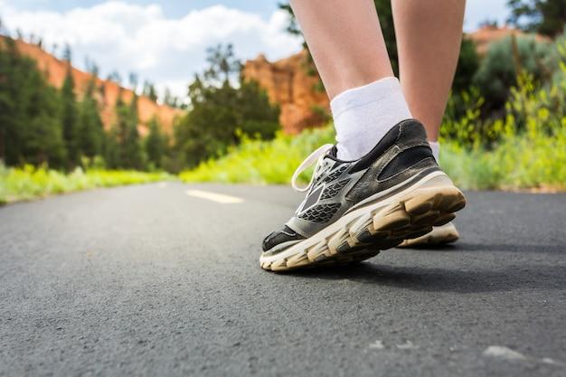 Ноги в спортивной обуви на дороге на закате крупным планом.