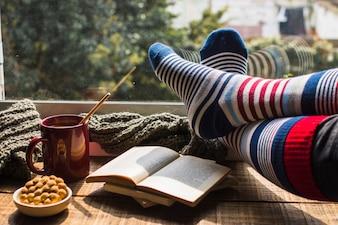 Legs in striped socks near window