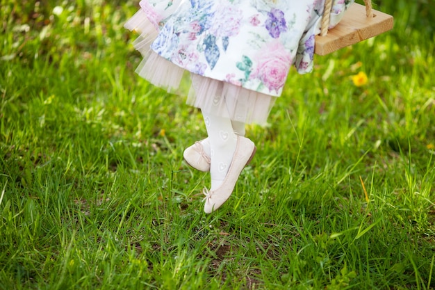 Legs of  little girl. having fun in the village. details dresses, white socks and shoes.  childhood. summer holidays. swing. happy and funny life time