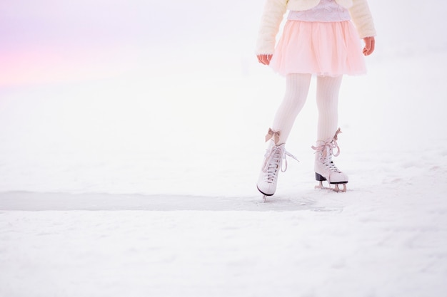 Legs of little girl skating on ice in morning light at dawn.
