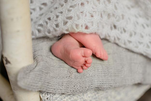 Ноги маленькой новорожденной девочке восьми дней в красивом наряде, который спит мило