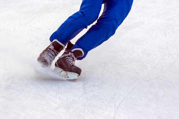 Legs of a man in ice skates actively skates on an ice rink in winter. hobbies and sports.