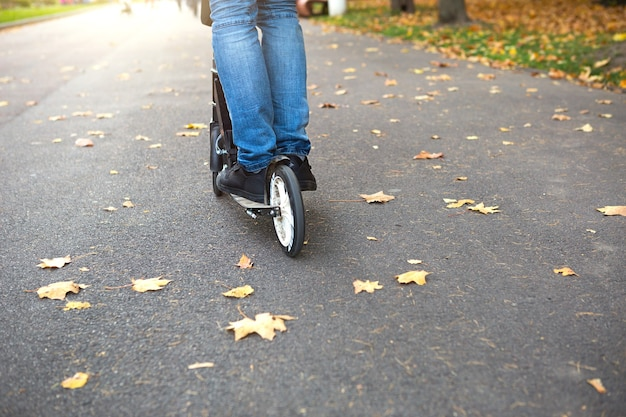 The legs of a man in jeans and sneakers on a scooter in the park in autumn with fallen dry yellow leaves on the asphalt. autumn walks, active lifestyle, eco-friendly transport, traffic