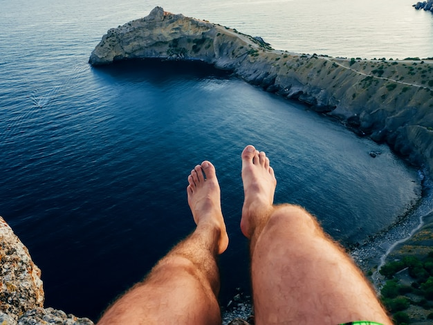 Legs of a man sitting on a mountain above the sea in the tourist camping