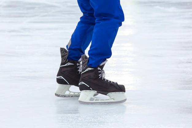 Legs of a man skating on an ice rink. hobbies and sports. vacations and winter activities.