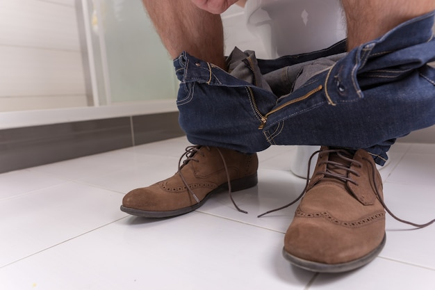 Legs of man wearing jeans sitting on a toilet bowl in  the modern tiled bathroom at home