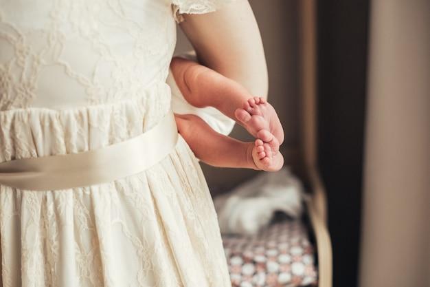 다리 신생아. 엄마는 아기를 유지