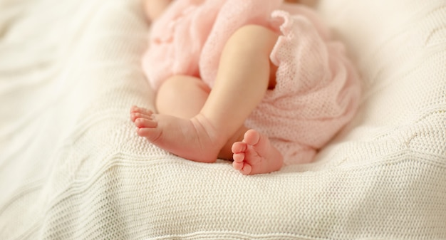 The legs of a newborn baby wrapped in a pink blanket lying on a white knitted blanket . selective focus.
