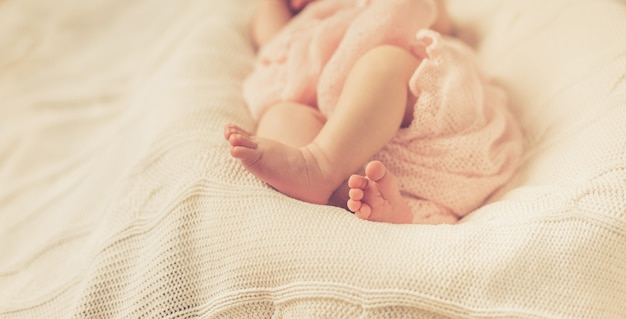 The legs of a newborn baby wrapped in a pink blanket lying on white