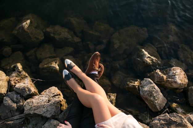 海の横にある岩に夫婦の美脚