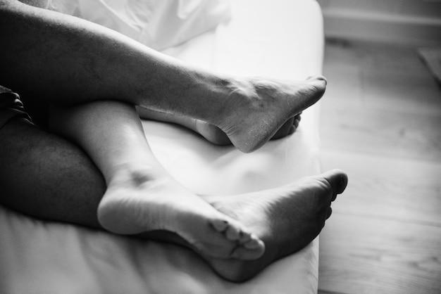 ベッドで寝ているカップルの足