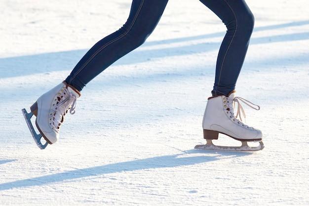 얼음 반지에 청바지와 흰색 스케이트에 여자의 다리