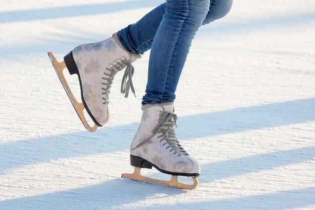 아이스 링크에서 청바지와 흰색 스케이트에 여자의 다리.