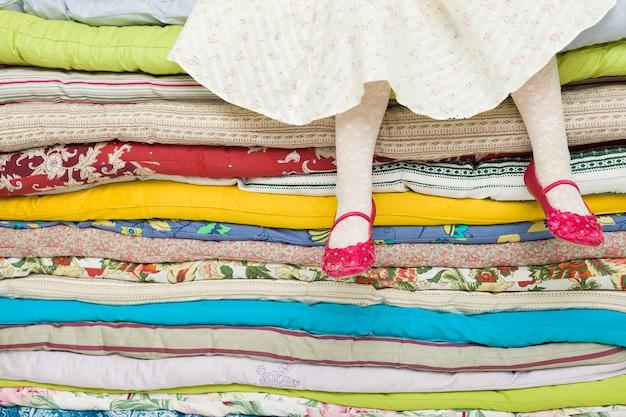 완두콩에 공주 동화에 대한 매트리스 장식 더미에 앉아있는 소녀의 다리