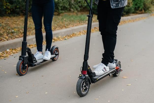 電動スクーターに乗る男と女の足のクローズアップ