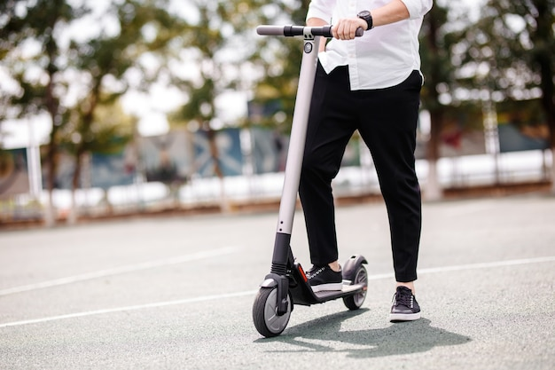 スタイリッシュな服装の男の足が通りの電動スクーターに立っています。