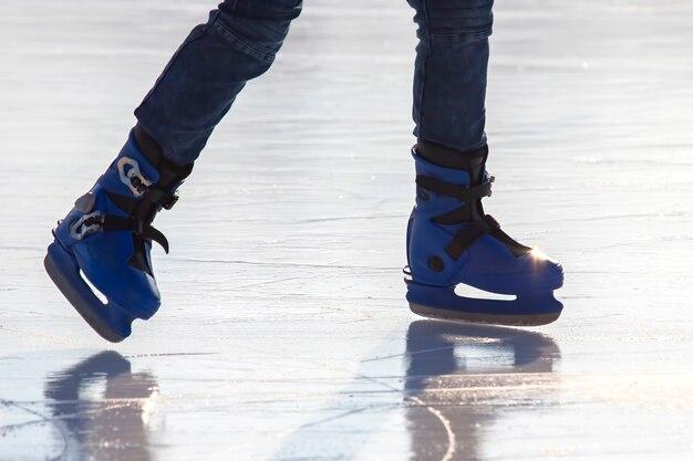 アイススケートリンクでスケートをしている男の足。趣味とスポーツ。休暇や冬のアクティビティ。