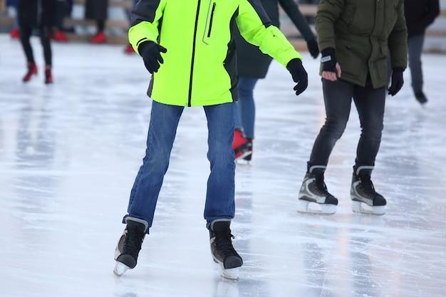아이스 링크에서 스케이트를 타는 남자의 다리. 취미와 스포츠. 휴가 및 겨울 활동