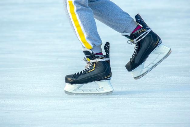 아이스 링크에서 스케이트를 타는 남자의 다리. 취미와 스포츠. 휴가 및 겨울 활동.