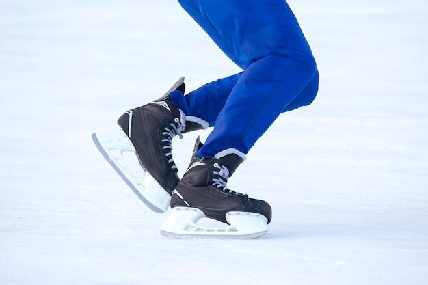 아이스 링크에서 스케이트를 타는 남자의 다리. 취미와 스포츠.