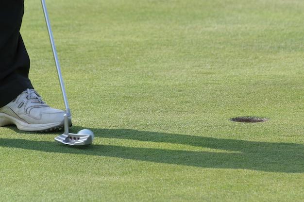 필드에서 골프를 치는 사람의 다리